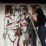 Photo de Maria Delacour en train de peindre sur tissus des corps de femmes